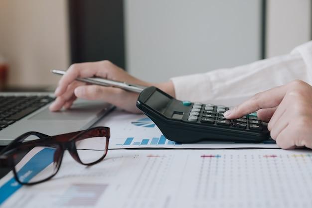 Femme affaires, utilisation, calculatrice, et, ordinateur portable, pour, faire, math, finance, sur, bureau bois, dans, bureau