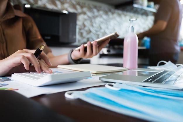 Femme affaires, utilisation, calculatrice, et, ordinateur portable