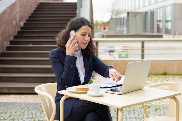 Femme affaires, utilisation, ordinateur portable, smartphone, café