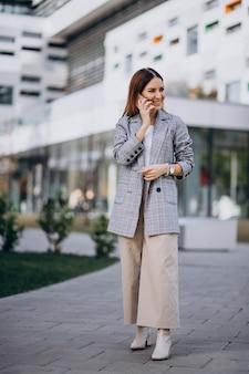 Femme affaires, utilisation, téléphone, dehors, rue, bâtiment