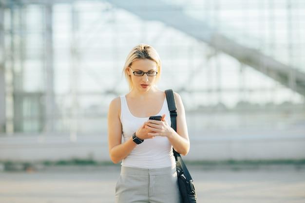 Femme affaires, utilisation, a, téléphone, et, horloge, quoique, debout, dans, extérieur