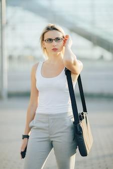 Femme affaires, utilisation, a, téléphone, et, horloge, quoique, debout, devant, bâtiment