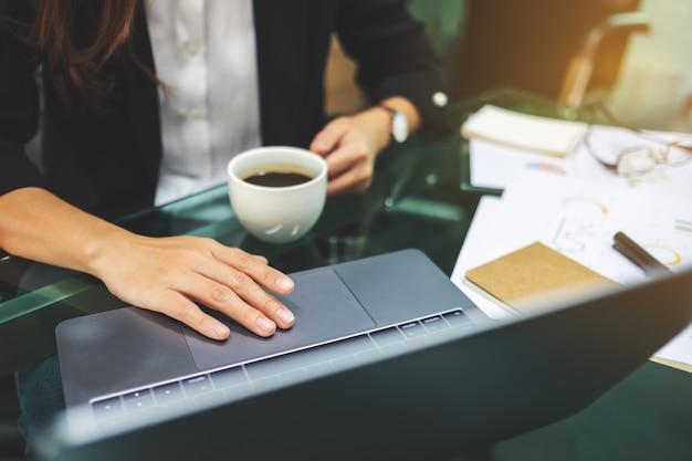 Femme affaires, utilisation, toucher, ordinateur portable, touchpad, quoique, boire, café, bureau