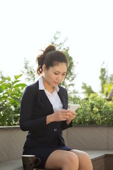 Une femme d'affaires utilise un smartphone dans le parc du jardin