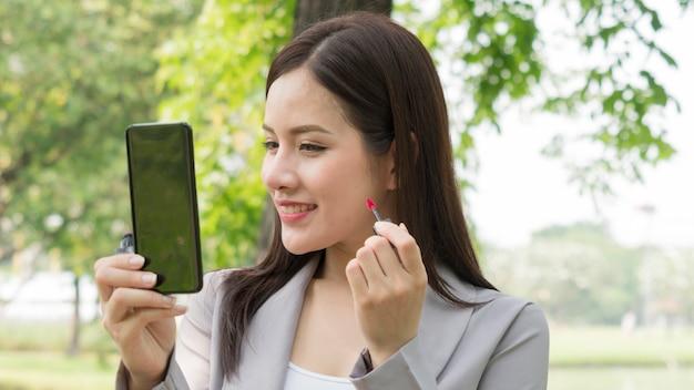 Femme d'affaires utilise un smartphone pour maquiller son visage avec du rouge à lèvres