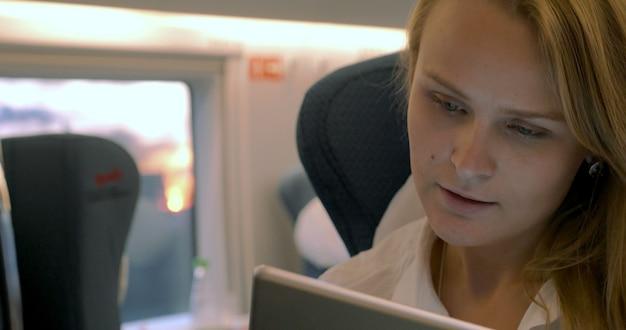 La femme d'affaires utilise la tablette électronique dans le train