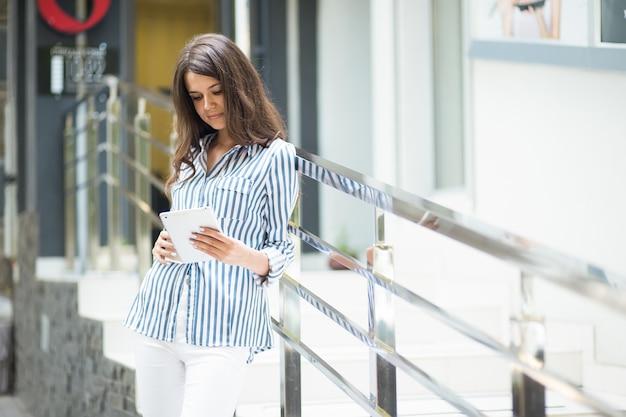 Femme d'affaires utilise une tablette, marchant le long.