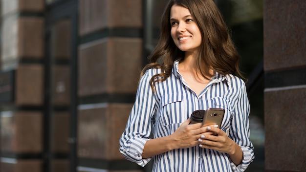 Femme d'affaires utilise un téléphone mobile, marchant le long.