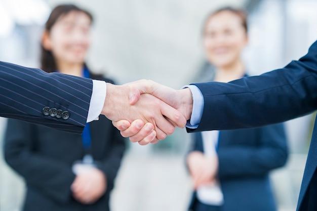 Femme d'affaires veillant sur la poignée de main avec un sourire
