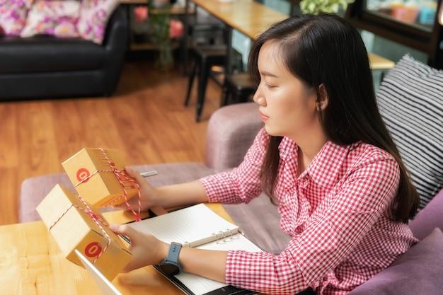 Femme d'affaires avec vente en ligne et expédition de colis dans son bureau à domicile.