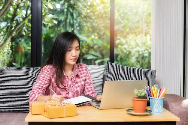 Femme d'affaires avec vente en ligne et expédition de colis dans son bureau à domicile