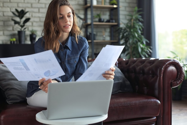 Femme d'affaires vérifiant les documents papier au bureau à domicile, travaillant sur un ordinateur portable depuis la maison.