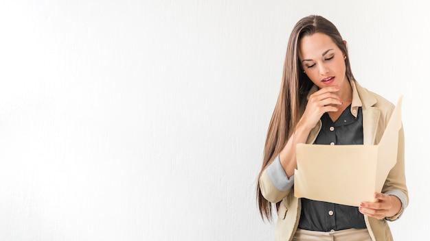 Femme d'affaires vérifiant les notes avec espace de copie