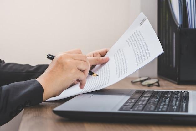 Femme d'affaires vérifiant le papier, travaillant avec ordinateur portable et des documents sur son bureau