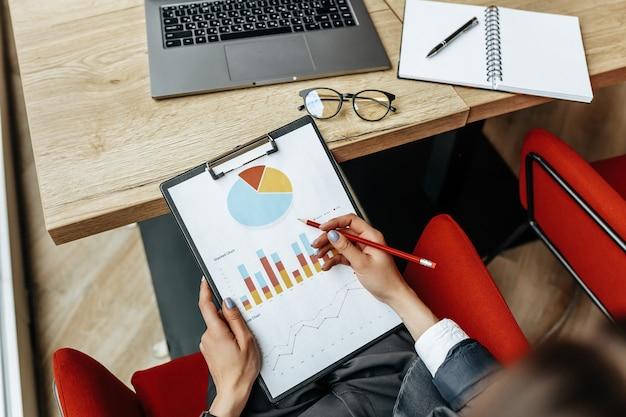 Une femme d'affaires vérifie les graphiques et actualise les progrès financiers. la jeune fille analyse le modèle commercial sur le lieu de travail.