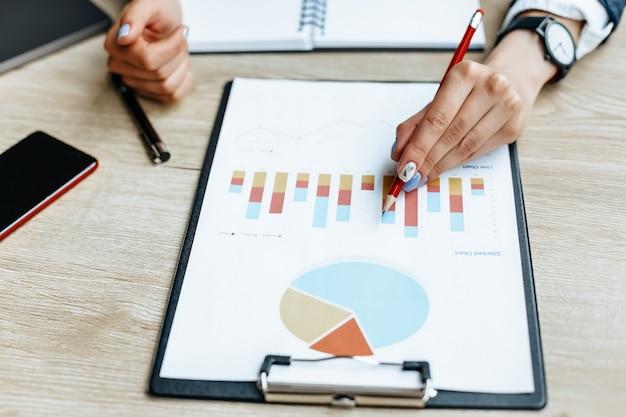 Femme d'affaires vérifie les graphiques et actualise les progrès financiers