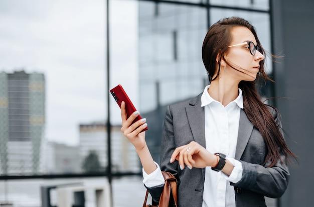 Une femme d'affaires vérifie l'heure dans la ville pendant une journée de travail en attendant une réunion. discipline et timing. un employé se rend à une réunion d'entreprise.