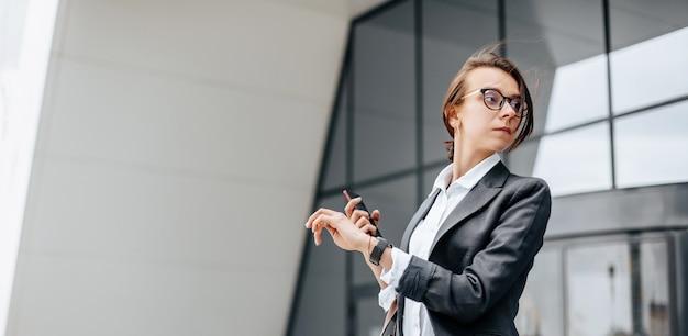 Une femme d'affaires vérifie l'heure dans la ville pendant une journée de travail en attente d'une réunion.