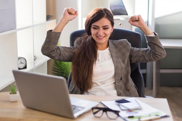 Femme d'affaires victorieuse au bureau avec ordinateur portable