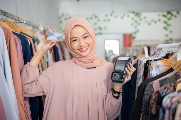 Une femme d'affaires voilée tenant une carte de crédit et une machine de capture de données électroniques
