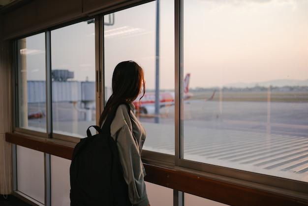 Femme d'affaires voyageuse portant un masque facial regardant vers l'avion, debout avec un sac à dos dans le terminal de départ de l'aéroport. vol de passagers féminins voyageant en avion pendant la pandémie du virus covid19.