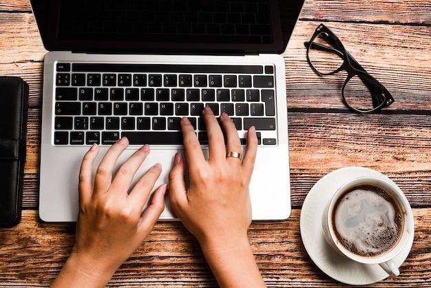 Femme d'affaires vue de dessus tapant sur ordinateur portable au lieu de travail.