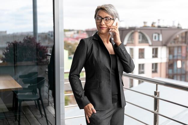 Femme d'affaires vue de face, parler au téléphone