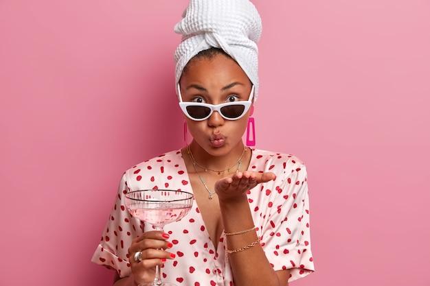 Une femme affectueuse à la peau sombre envoie un baiser d'air, garde les lèvres arrondies, tient un cocktail, porte des lunettes de soleil à la mode, une serviette sur la tête