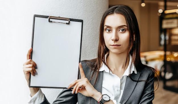 La femme affiche des informations sur la tablette. lieu de publicité. concept d'entreprise. la fille tient les documents et explique les informations. feuille de papier vierge blanche.