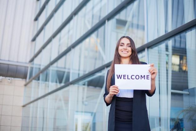 Femme avec l'affiche avec message de bienvenue