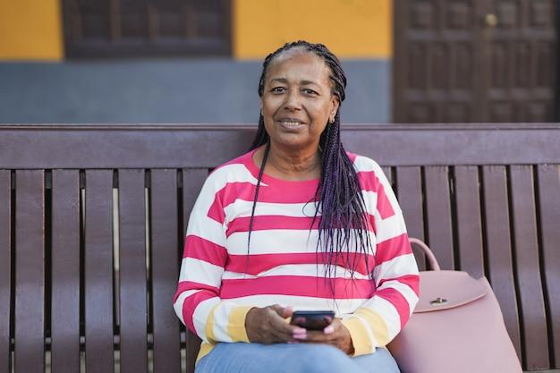 Femme africaine âgée assise sur un banc dans la ville tout en tenant son smartphone dans les mains