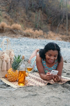 Femme africaine allongée sur la plage vérifiant son téléphone portable