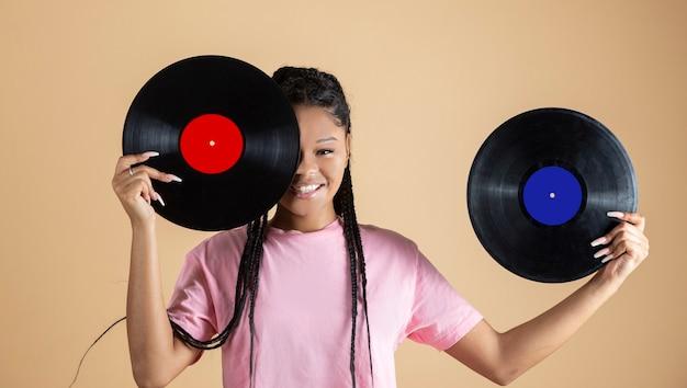 Femme africaine assez mélangée avec des vinyles sur son visage, fond beige