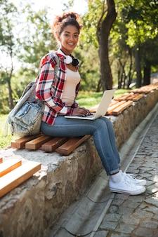 Femme africaine assise à l'extérieur dans le parc.