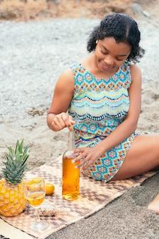 Femme africaine assise sur la plage en débouchant une bouteille de vin