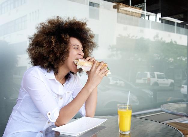 Femme africaine au café, manger un sandwich