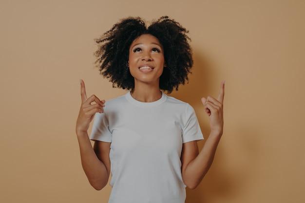 Femme africaine bouclée pointant avec les index vers le haut sur l'espace de copie contre le mur du studio marron