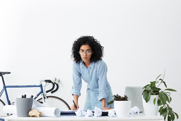 Femme africaine concentrée écrit quelque chose sur des papiers, debout devant la table