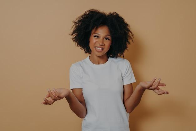 Une femme africaine confuse ne peut pas prendre de décision, haussant les épaules isolées sur fond beige