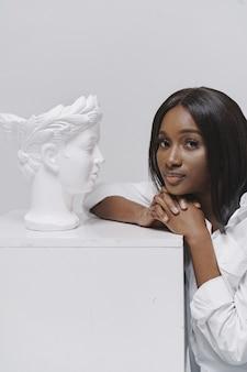 Femme africaine dans un studio. mur blanc. femme en chemise blanche.