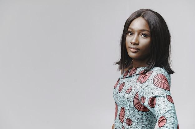 Femme africaine dans un studio. mur blanc. femme en robe bleue.
