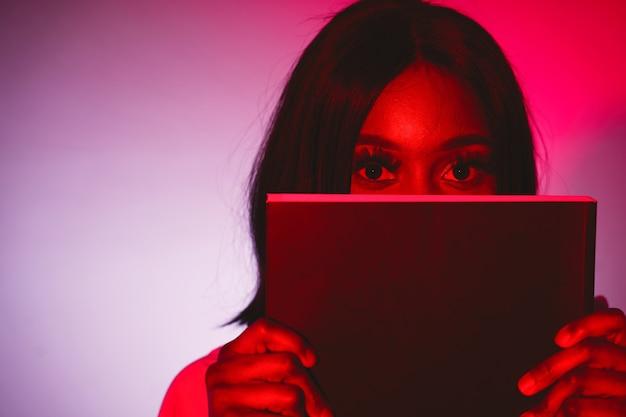 Femme africaine dans un studio. mur rouge. femme en chemise blanche.