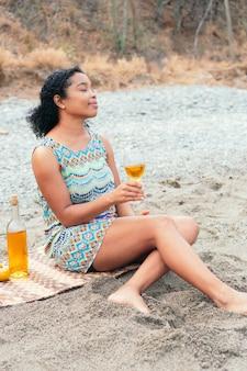 Femme africaine dégustant un verre de vin sur la plage le matin