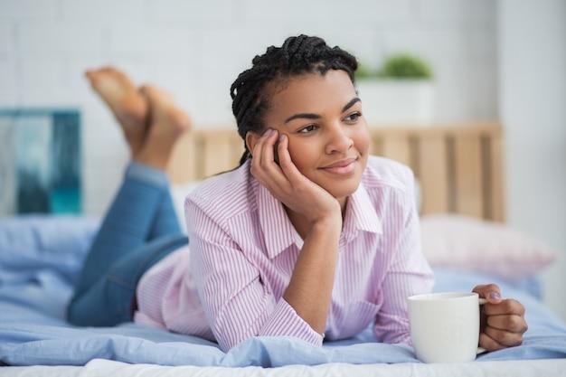 Une femme africaine détendue qui boit du thé au lit