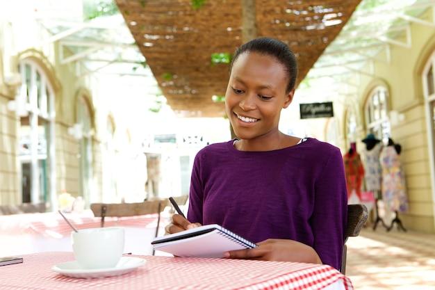 Femme africaine écrivant dans un café