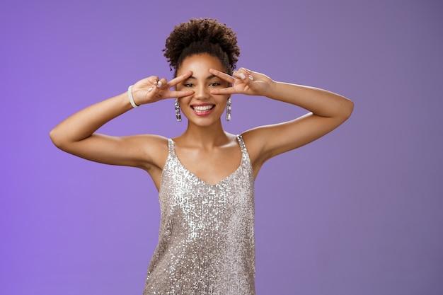 Une femme africaine élégante et souriante charismatique en robe de cocktail scintillante argentée montre un geste de paix chanceux de victoire danse disco souriant joyeusement diverti debout fond bleu positif.