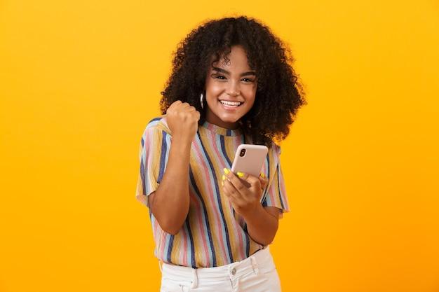 Femme africaine émotionnelle posant isolée sur un espace jaune à l'aide de téléphone mobile faire le geste gagnant.