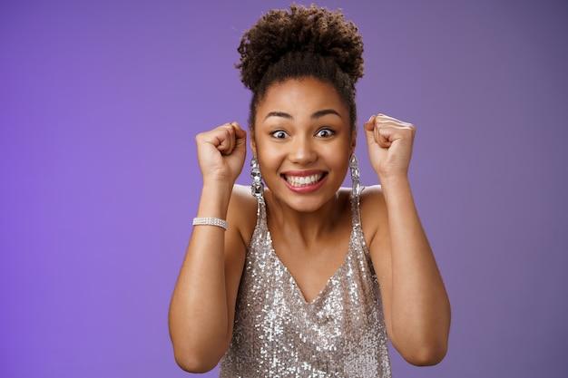 Femme africaine excitée dans une élégante robe argentée brillante souriante ravie de gagner le poing levé...