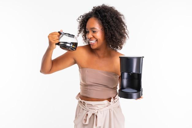 Femme africaine gaie dans des vêtements d'été avec cafetière, photo isolé sur fond blanc