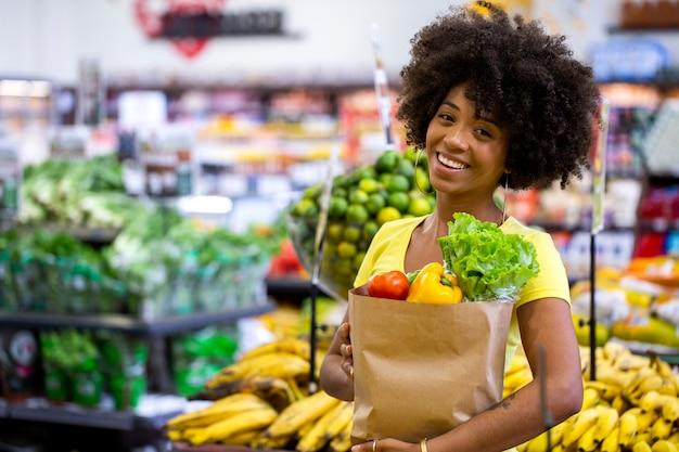 Femme africaine heureuse positive saine tenant un sac à provisions en papier plein de fruits et légumes.